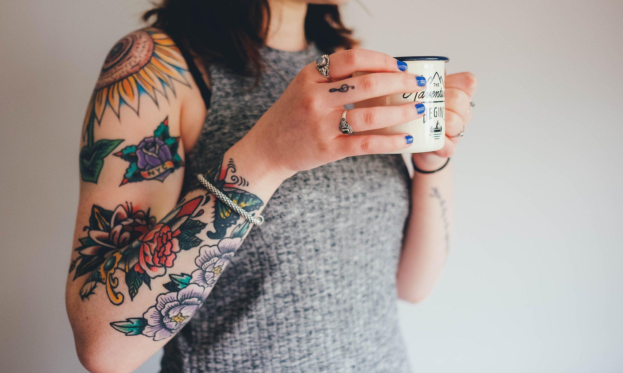 Kobieta z tatuażami trzyma kubek