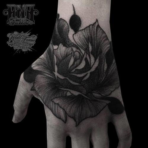 Kwiat na dłoni cieniowany techniką dotwork
